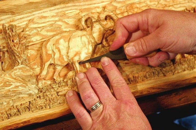 Hands working on an elephant carving